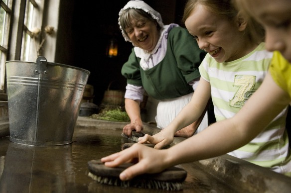 Children with a costumed interpreter learning how to scrub the table clean in the Kitchen at the Apprentice House at Quarry Bank Mill, Styal, Cheshire