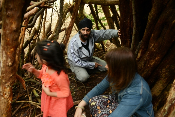 Family discover a den built on the Natural Play trail at Box Hill, Surrey.