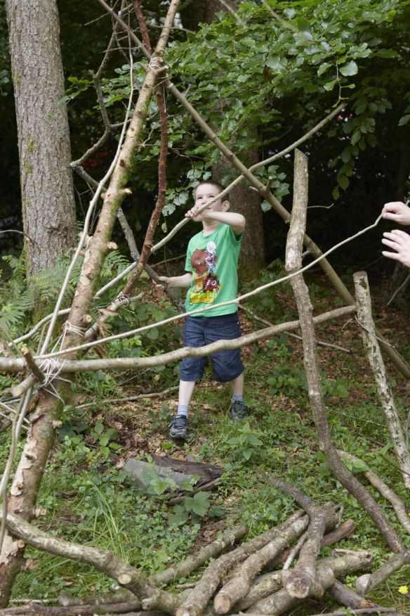 Child building a den in the grounds at Wray Castle, Cumbria.
